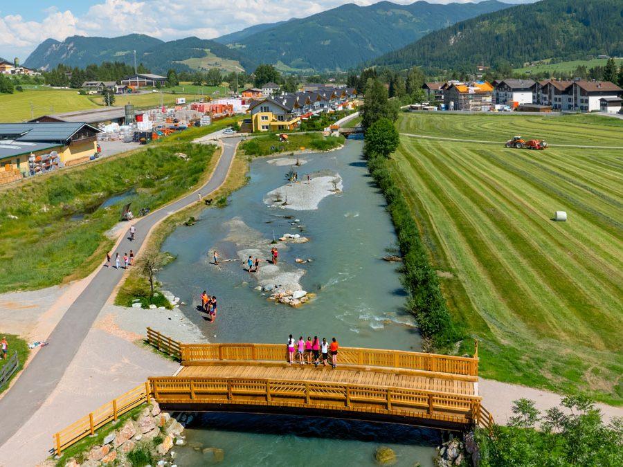 Enns-Salzburg: Flussabschnitt mit kleinen Schotterinseln, umgeben von Wiesen und einem Dorf. Menschen stehen auf Brücke, einige stehen im Fluss oder gehen entlang spazieren.