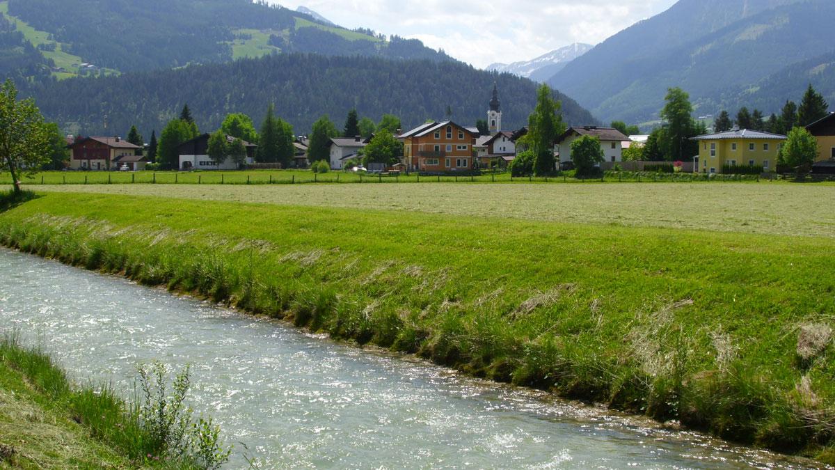 Salzburg-Enns. Flussabschnitt der Enns in Altenmarkt. Landschaftsbild mit Fluss im Vorder- und Dorf im Hintergrund.