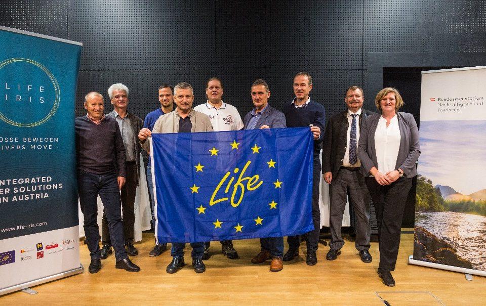 Auftakt für LIFE IRIS: Projektleiter halten Fahne mit Life-Logo.