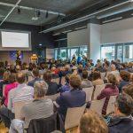 Bild vom Veranstaltungsraum mit Gästen und Präsentation